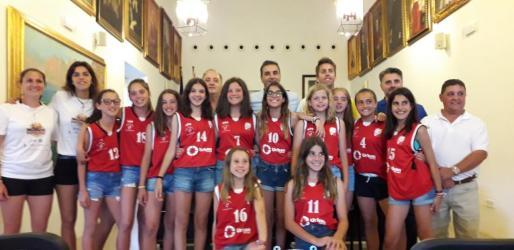 Las jugadoras mini del Club Bàsquet Pollença en la sala de plenos del ayuntamiento junto al alcalde Bartomeu Cifre y a Sete Benavides.