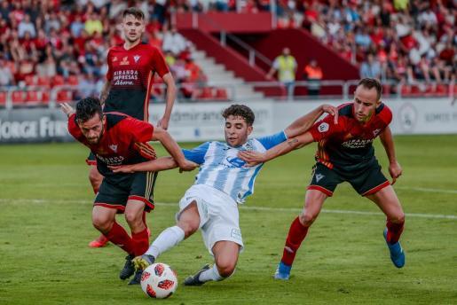 El jugador del Atlético Baleares, Samuel Shashoua, puja por un balón entre dos jugadores del Mirandés.