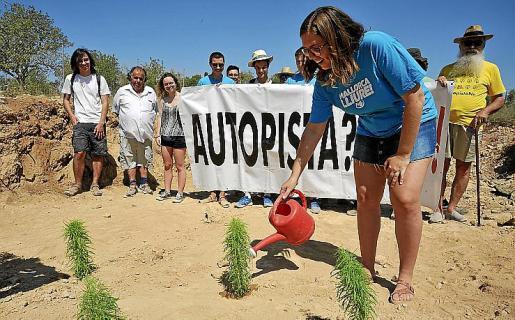 Una de las activistas riega una de las simbólicas plantas.