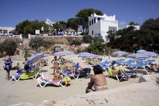 Veraneantes disfrutando de la playa en Sa Caleta, en Menorca, el verano pasado.
