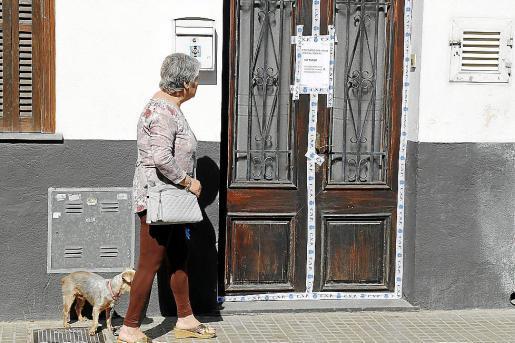 Una mujer pasa junto a la puerta de la vivienda de la víctima en s'Arenal.