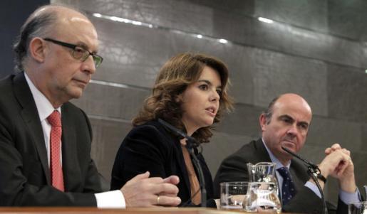 De izquierda a derecha, el ministro de Hacienda, Cristóbal Montoro, la portavoz del Gobierno, Soraya Sáena de Santamaría, y el ministro de Economía, Luis de Guindos.