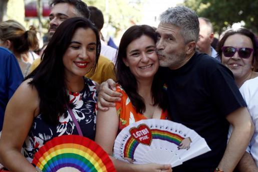 El ministro del Interior en funciones, Fernando Grande Marlaska, besa a la exministra de Sanidad, Carmen Montón (c), en presencia de la secretaria de Movimientos Sociales del PSOE, Mónica Silvana (i), momentos previos a la manifestación del Orgullo 2019.