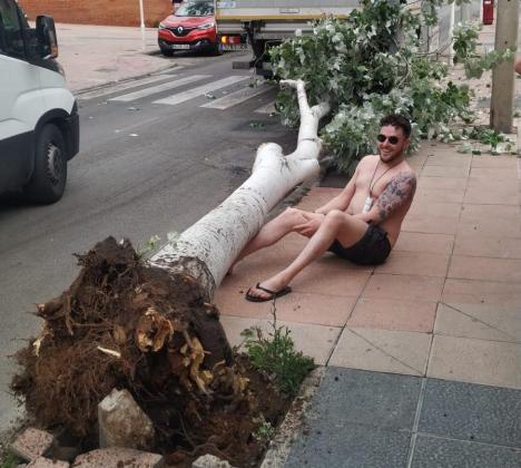 Un turista simulando que el árbol se le ha caído encima.
