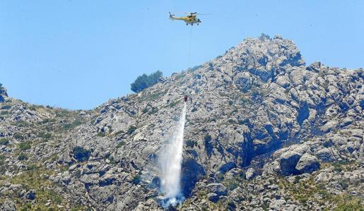Un helicóptero descarga agua sobre el perímetro del incendio de Cala Tuent.