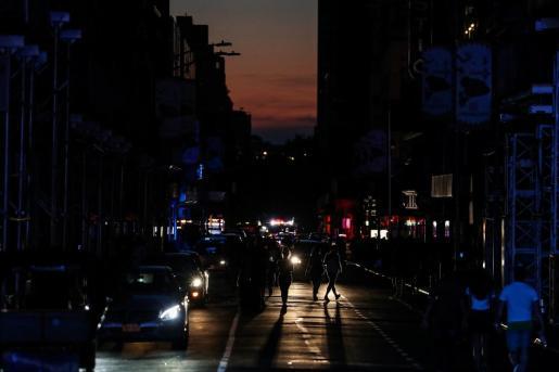 Varias personas caminan a oscuras por Times Square, en Manhattan, durante el corte eléctrico masivo.