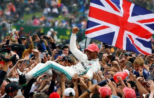 El piloto británico de Fórmula Uno Lewis Hamilton, de Mercedes AMG GP, celebra su victoria este domingo en el Gran Premio de Gran Bretaña, décima prueba del Mundial de Fórmula Uno que se disputó en el circuito de Silverstone , en Northamptonshire, Gran Bretaña.