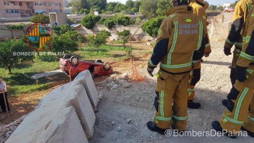 Los bomberos de Palma junto al vehículo que ha sufrido el vuelco.