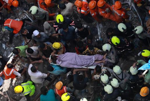 Miembros de los servicios de rescate retiran el cadáver de una víctima tras el derrumbe de un edificio en Bombay (India) este martes.