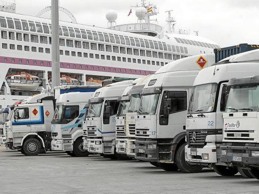Una hilera de camiones espera en la plataforma del puerto.