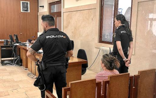 La acusada, este lunes en el juicio, custodiada por dos agentes de la Policía Nacional.