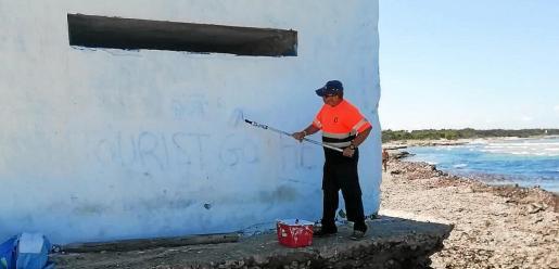Un miembro de la brigada municipal de Campos tapando una pintada.