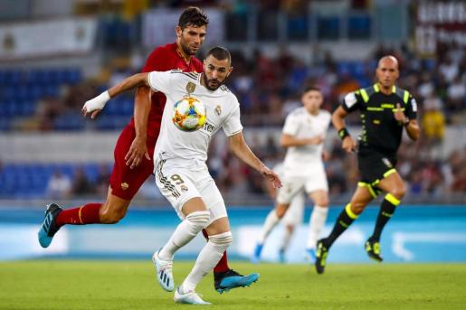 El defensa de la Roma Federico Fazio persigue al delantero del Real Madrid Karim Benzema.