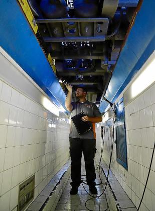 Un operario de la estación de Som Oms inspecciona un vehículo.