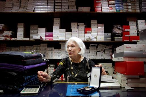Dolores Agra, propietaria de la lencería Marta, en el barrio coruñés de Os Castros, muestra la medalla al Mérito por el Trabajo, concedida cuando superó los 61 años de cotización.