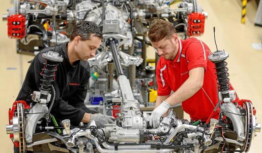 Dos trabajadores montan un deportivo en una línea de ensamblaje de Porsche en Stuttgart, Alemania.