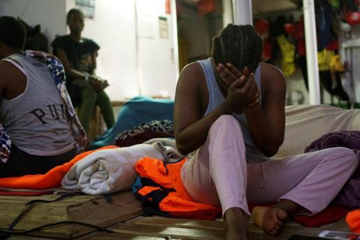 Uno de los 134 inmigrantes que lleva a bordo el Open Arms en la cubierta del buque la noche del viernes.