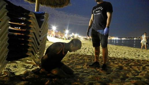 Un detenido junto a un agente en la Playa de Palma.