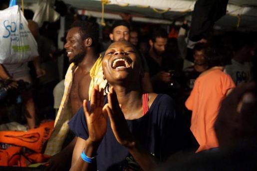 Varios migrantes esperan celebrando la decisión de la Fiscalía italiana.