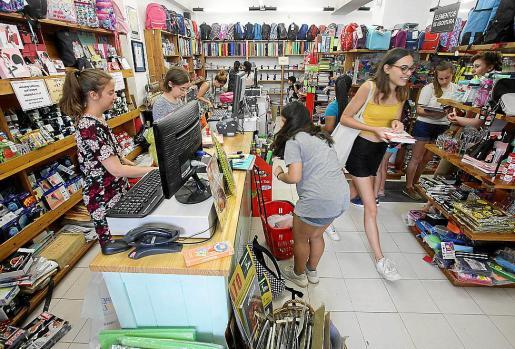 Varias personas adquieren artículos de material escolar en una tienda especializada.