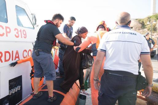 Una mujer, ayudada a desembarcar en Lampedusa.