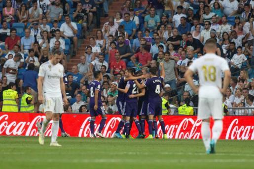 Los jugadores del Valladolid celebran el tanto del empate en el Santiago Bernabéu ante unos cabizbajos Bale y Jovic.