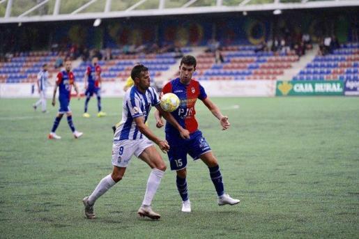 El jugador del Atlético Baleares Toni Gabarre pugna con un rival en el partido disputado este domingo en el Nuevo Ganzábal de Langreo.
