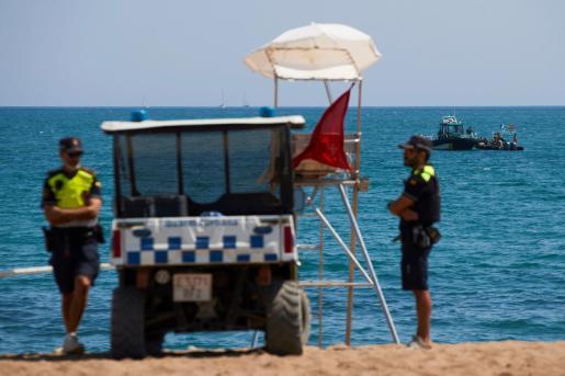 Buzos del Grupo Especial de Actividades Subacuáticas de la Guardia Civil en la playa de San Sebastian de la Barceloneta en Barcelona, que ha sido desalojada por la presencia de un artefacto explosivo en el mar.