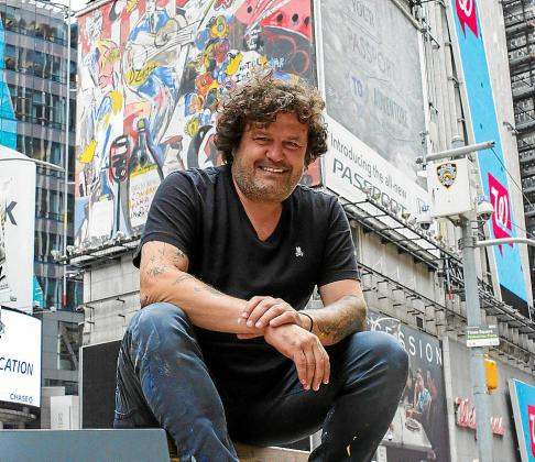 El artista español Domingo Zapata posa junto al mural que pintó en Times Square, en Nueva York (EE.UU.), un lienzo que envuelve tres paredes de quince pisos del emblemático One Times Square, el edificio que da la bienvenida al nuevo Año.