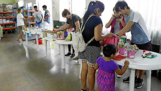 Los voluntarios, mientras introducen el material escolar en las mochilas.