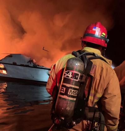 Un bombero trabajando en las labores de rescate del barco incendiado.
