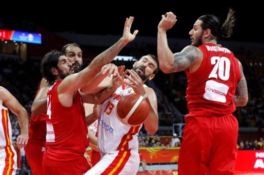 El pívot de la selección española de baloncesto Marc Gasol lucha por el balón con los jugadores de Irán, el ala-pívot Michael Rostampour y el escolta Nikkhah Bahrami, durante el partido de la primera fase de grupos.
