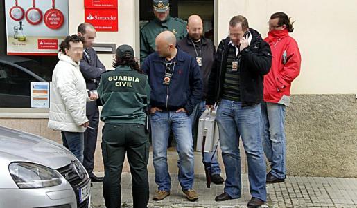 Agentes de la Policía Judicial de la Guardia Civil con compañeros uniformados y la empleada atracada.