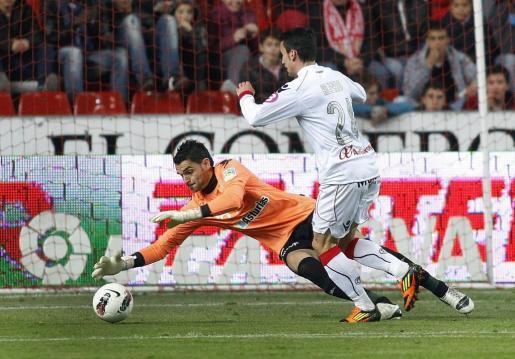 El delantero del Real Mallorca Alejandro Alfaro (d) presiona al portero del Sporting de Gijón, Juan Pablo, en su partido correspondiente a la vigésima novena jornada de la liga de fútbol en Primera División disputado en el estadio del Molinón de Gijón.