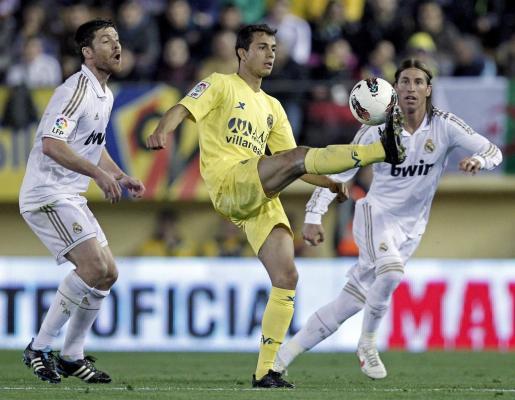 El brasileño Nilmar Da Silva (c), del Villarreal CF, controla el balón entre Xabi Alonso y Sergio Ramos, del Real Madrid.