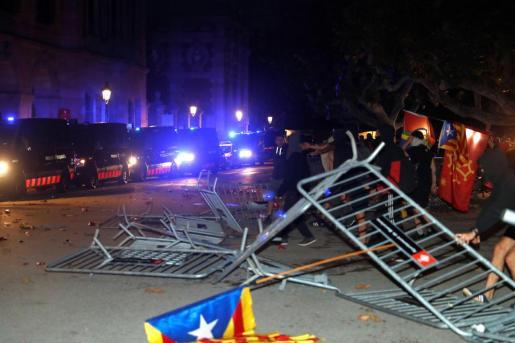 Un grupo de manifestantes derriban las vallas de seguridad frente al Parlament, durante la Diada.