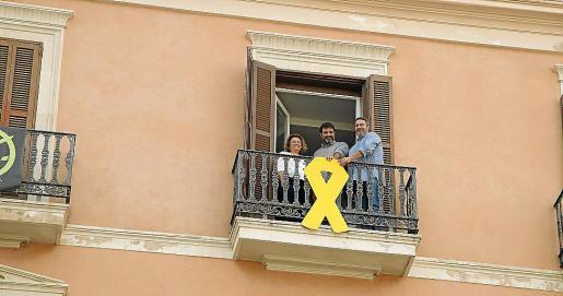 Cargos de Més posan tras el lazo amarillo de su balcón.