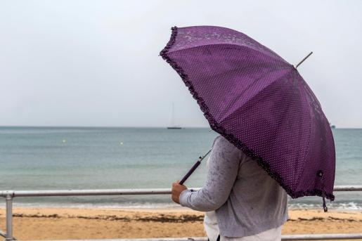Una mujer se protege de la lluvia este viernes en Palma.
