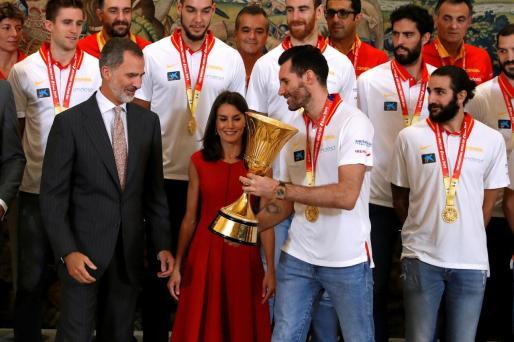 Los reyes reciben del capitán de la selección española de baloncesto Rudy Fernández la copa de campeones.