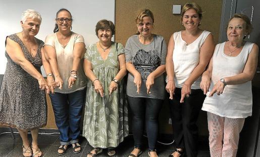 Margalida Terrassa, M. Ángeles Vera, Maria Ferragut, Ana Bauzá, Catalina Ramis y Ana M. Jiménez muestran el gesto con el que los miembros de la asociación identifican la enfermedad.
