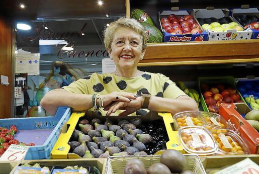 Cati Aguiló, este miércoles en el puesto de Ismael Cuenca, en el Mercat de l'Olivar, ante una caja de higos.
