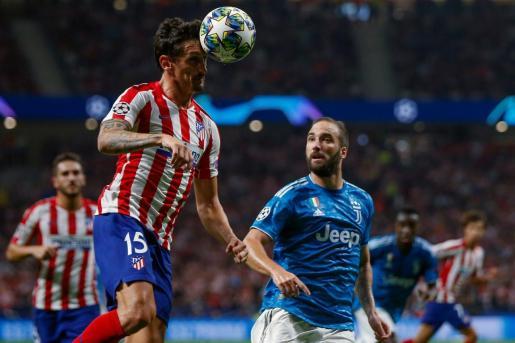 El defensa montenegrino del Atlético de Madrid Stefan Savic (i) despeja de cabeza junto al argentino Gonzalo Higuaín, de la Juventus.