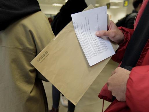 Una persona porta un sobre del voto por correo.