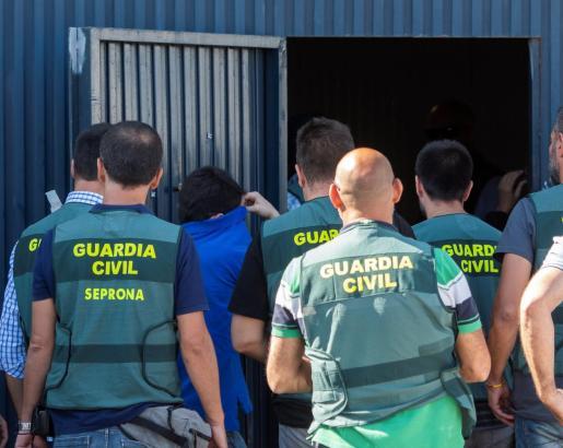 Uno de los responsables de la empresa Magrudis entra junto a los agentes de la Guardia Civil en las dependencias de la nave industrial.