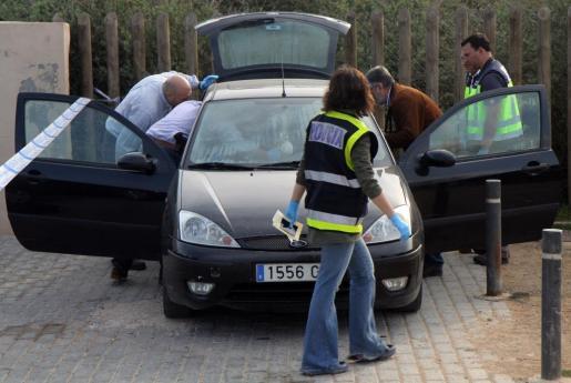 Agentes de la Policía Nacional inspeccionan el coche donde se ha encontrado a la pareja.