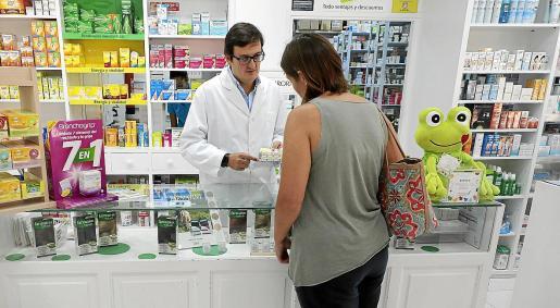 El farmacéutico Tomás Muret explica el funcionamiento de un dosificador a una clienta.