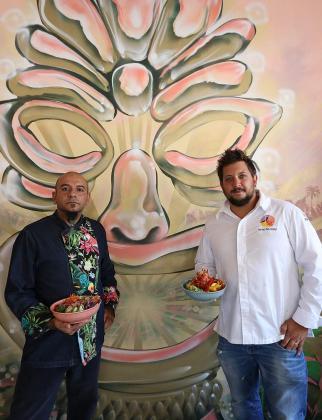 Javier González, cocinero de Shaka, y Matías Providenti sostienen dos boles de poke, uno de pescado mixto y otro de marisco.