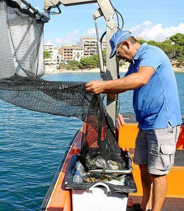 Las barcas recogen la basura con unas grandes redes.