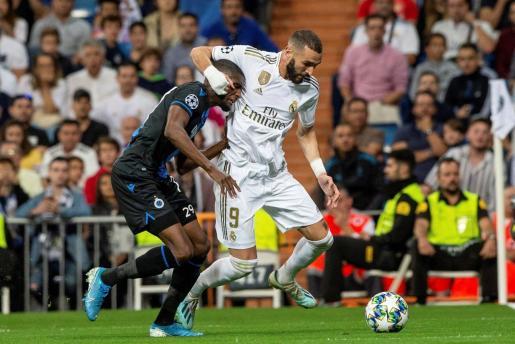 El delantero francés del Real Madrid Karim Benzema (d) disputa un balón con Krépin Diatta (i), delantero senegalés del Brujas.