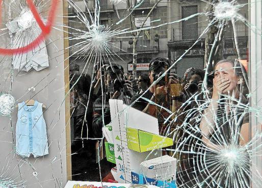 La dramática imagen de la encargada de una tienda cuando era atacada por radicales el día de la huelga general ha dado la vuelta a mundo. Mireia Arnau mostraba su desesperación ante los vándalos que atacaban la tienda porque dentro había una niña. Ha sido portada de The Washington Post.